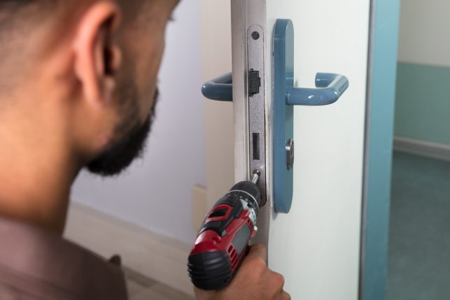 An image of a man using a drill to unscrew a lock