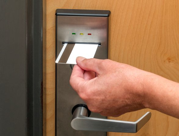 An image of someone using a card key to unlock a door