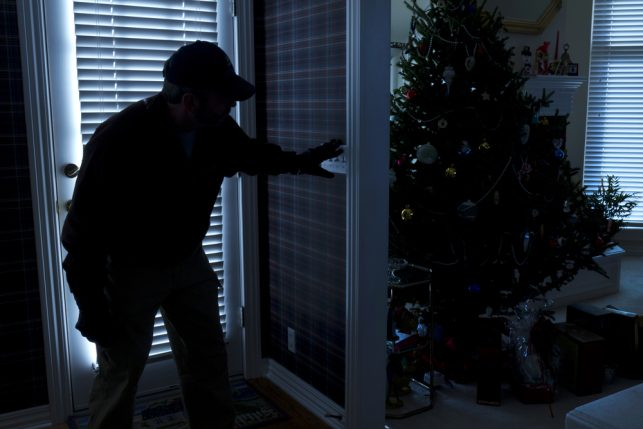 An image of a burglar gaining entry to a house at Christmas