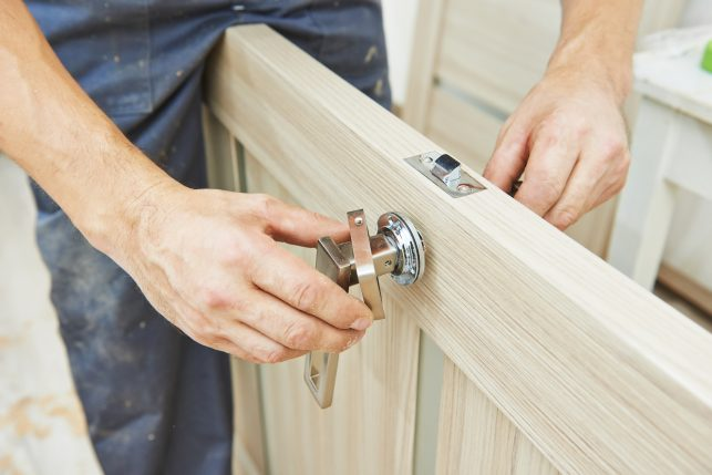 An image of a man fitting a handle to a wooden door