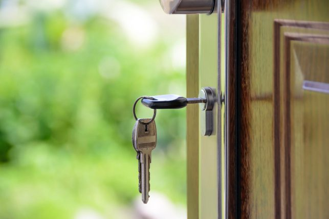 Image of a key in a front door, to emphasise need for better home security when a child is home alone.