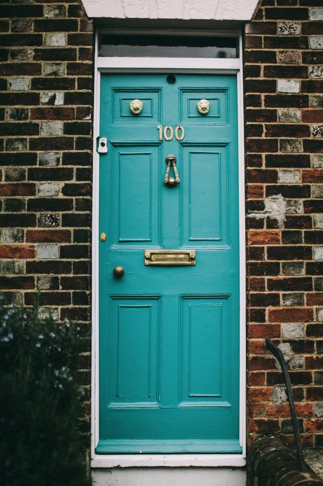 An image of a blue front door to a house, with a doorbell on the front. The front door could be even more secury by installing a home access control system, such as a video intercom.