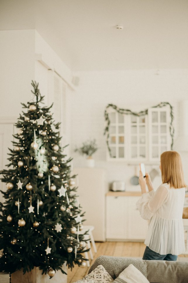 Image of a woman taking a photo of a christmas tree to share on social media. This can be a security breach at christmas time, as burglars can know where expensive gifts are kept under the tree.